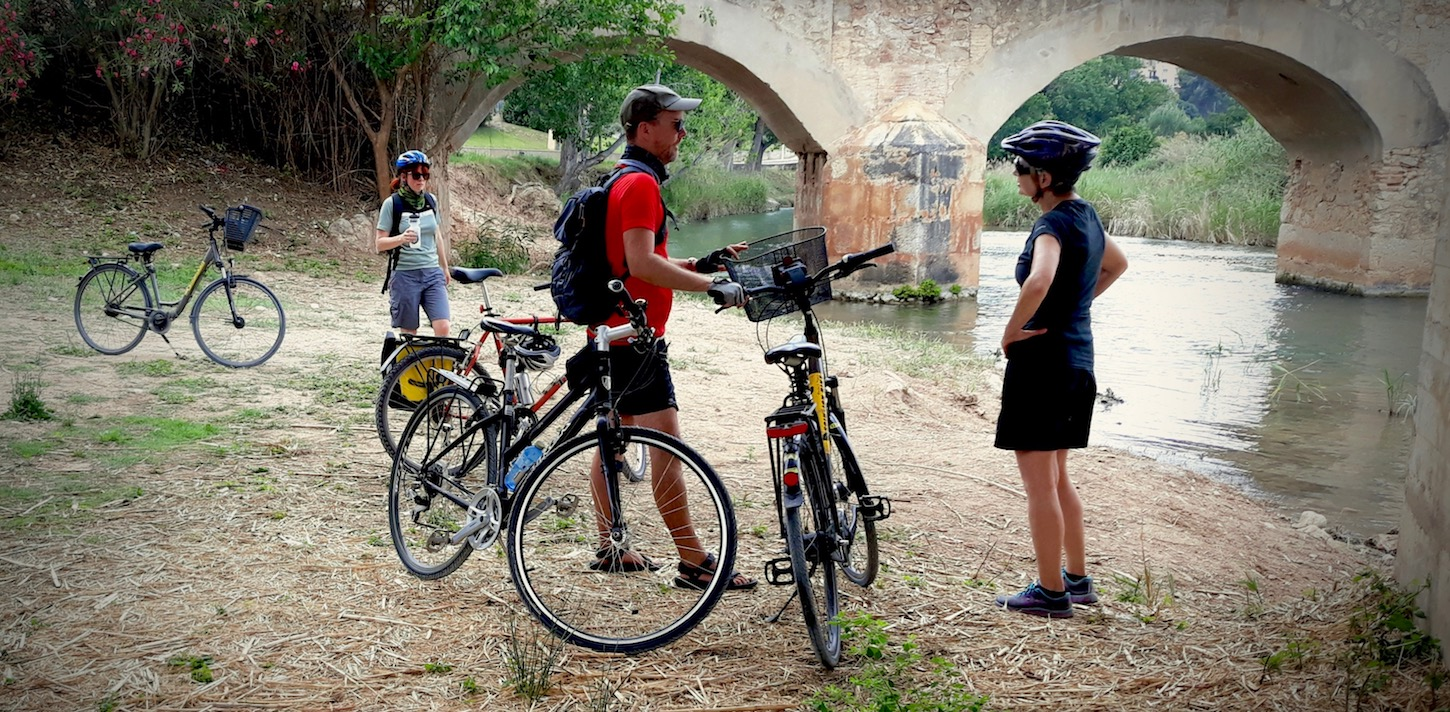 Three cyclist take a break along the Túria River