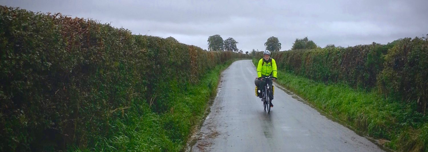 Cyclist on a narrow English rain on a rainy day