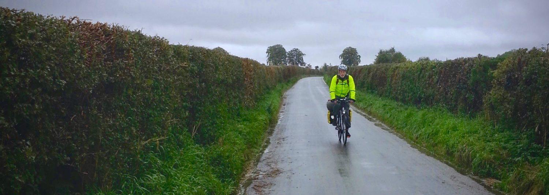 Cyclist on a narrow English rain on a rainy day