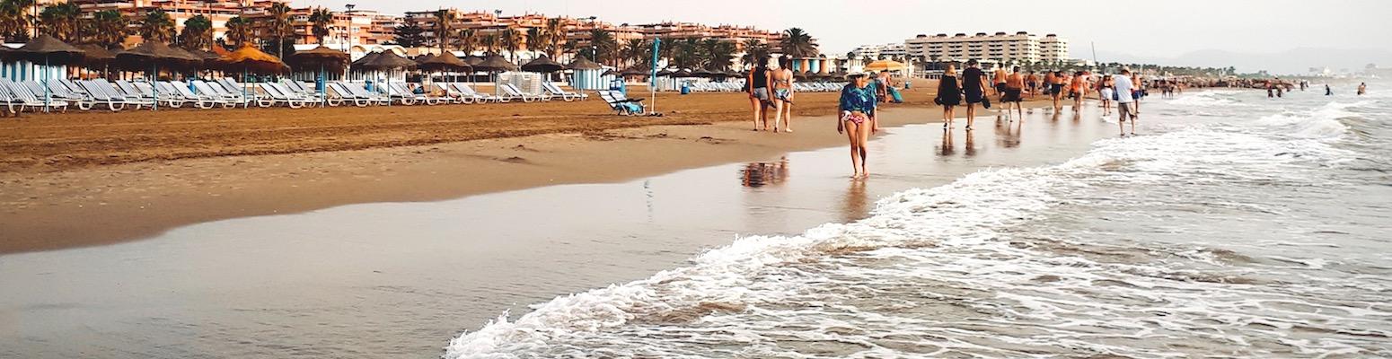 Beachgoers stroll and sunbathe at the water's edge.