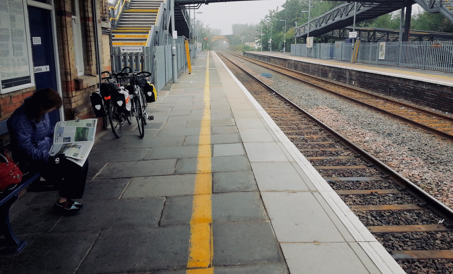 A cycle tourist waiting on a train platform in England