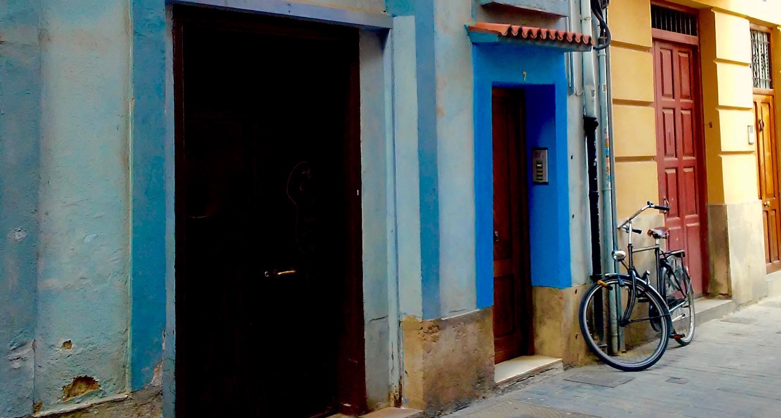 Old bicycle against a wall in a colorful Spanishstreet